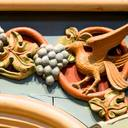 Carving of a bird with grapes. Where the side galleries meet the great columns, the wood carvers' fancy created colourful little animals.