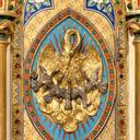 The golden bronze tabernacle is a splendid work of art, richly adorned with semi-precious stones. The motif adorning the door represents the pelican feeding its young with its own blood, a traditional Eucharistic symbol.
